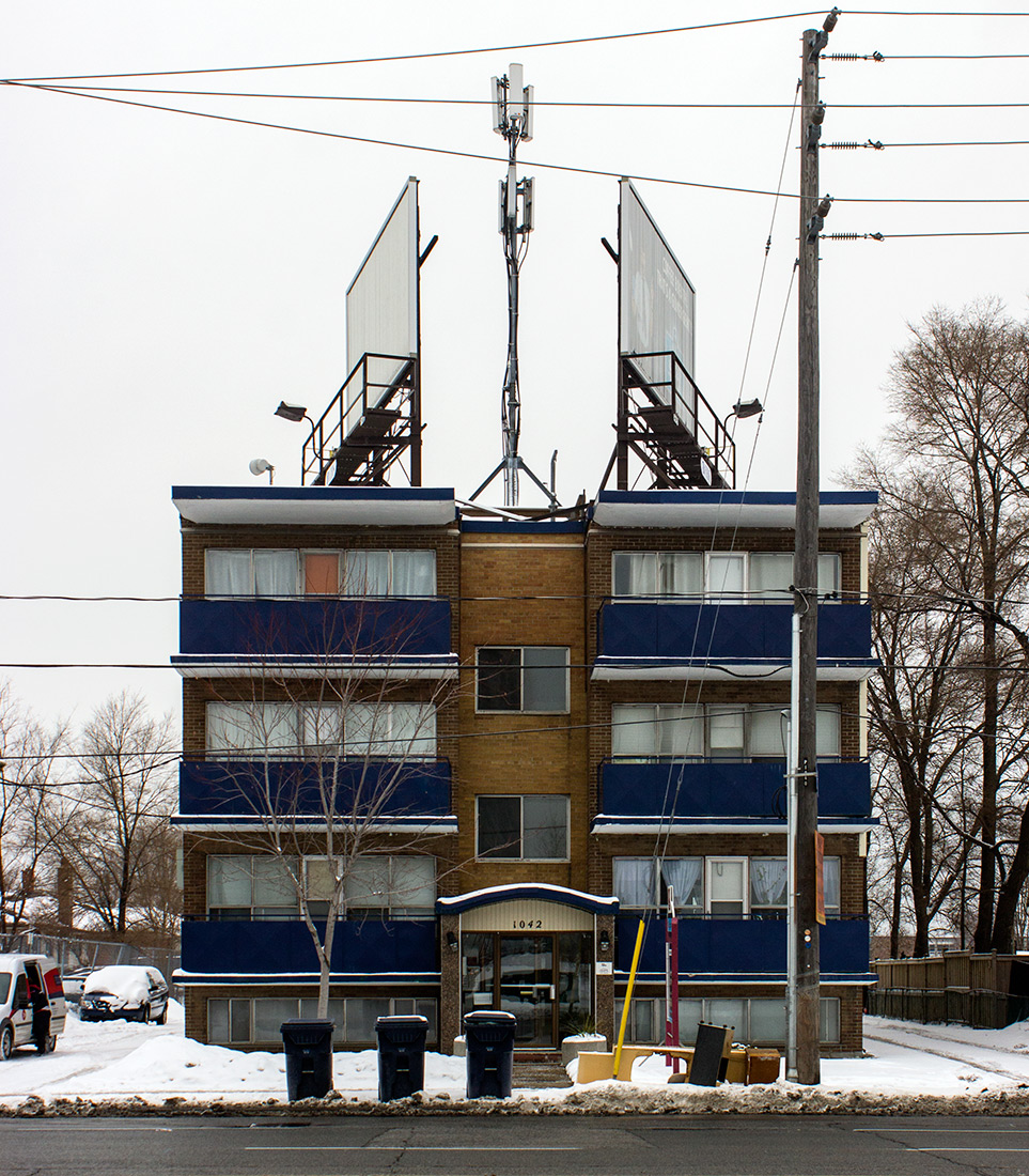 20140120. A cellphone tower and 2 billboards crown a tinyl apartment building at 1042 Sheppard Ave W, Toronto