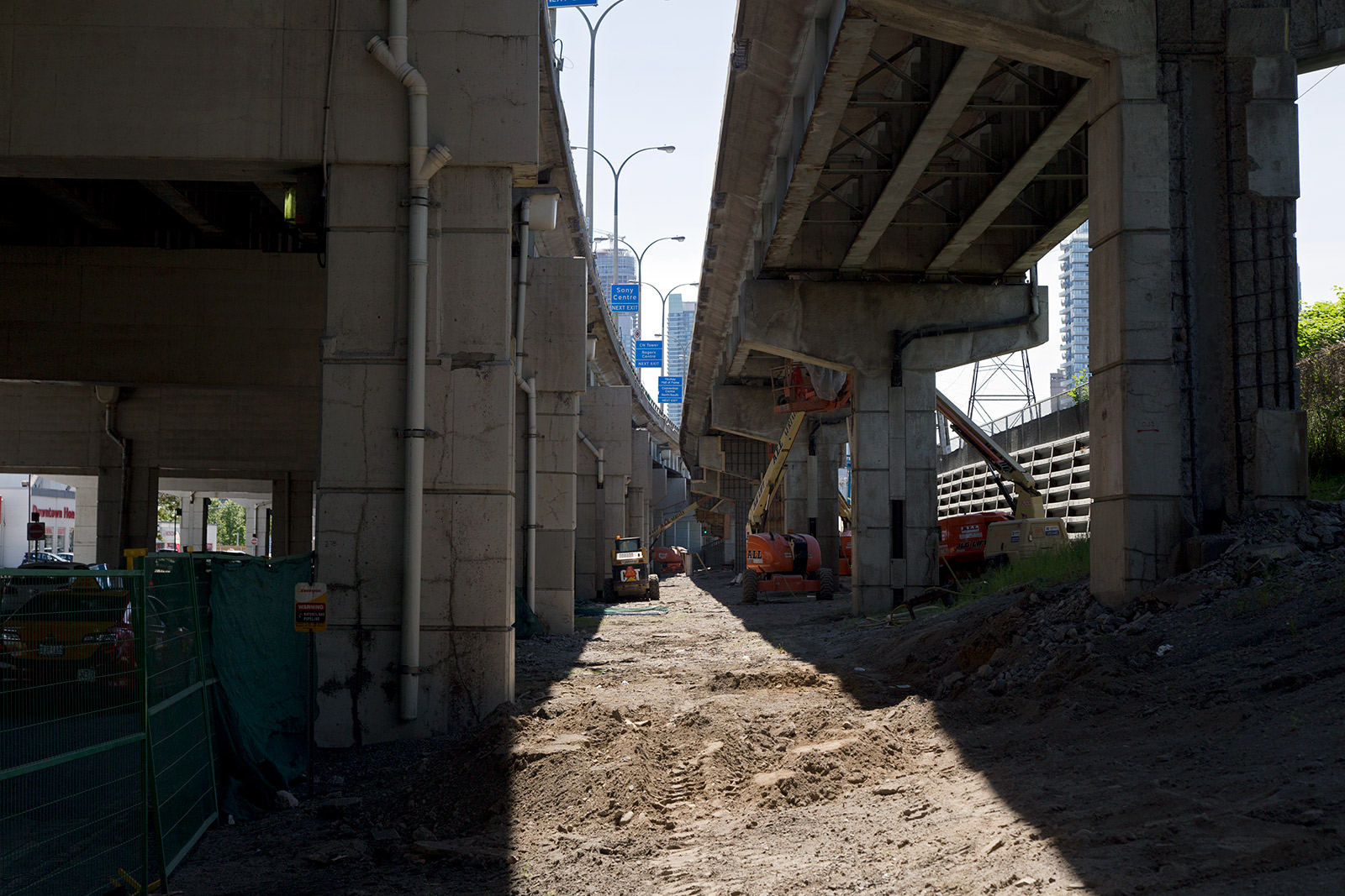 20140625. The sun shines between expressway and off-ramp under Toronto's Gardiner.